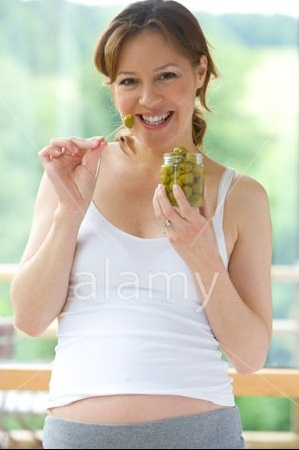 pregnant-woman-with-cravings-eating-olives-from-jar-bj0t41